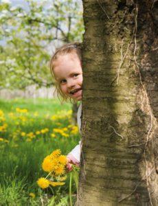Kind hinter Baum